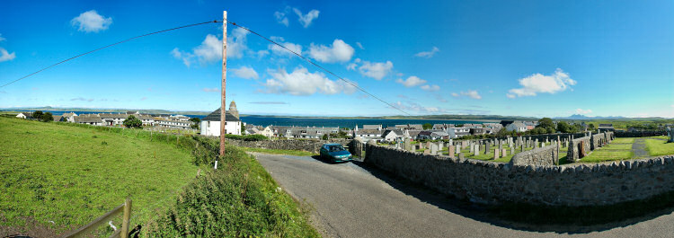 Picture of a panoramic view of a coastal village (Bowmore on the Isle of Islay) with a round church in the foreground. A large sea loch (Loch Indaal) in the background
