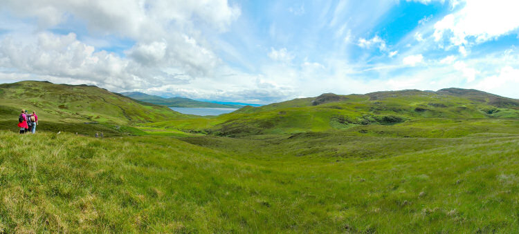 Picture of a panoramic view over a wide glen with a sound between two islands at the end