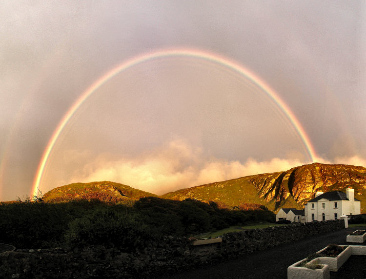 Picture of a full rainbow above crags and a house